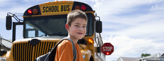 boy crossing in front of bus